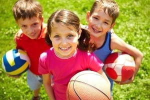 Two boys and a girl smiling holding basketball, volleyball, and soccer ball, standing on the grass looking up at the camera