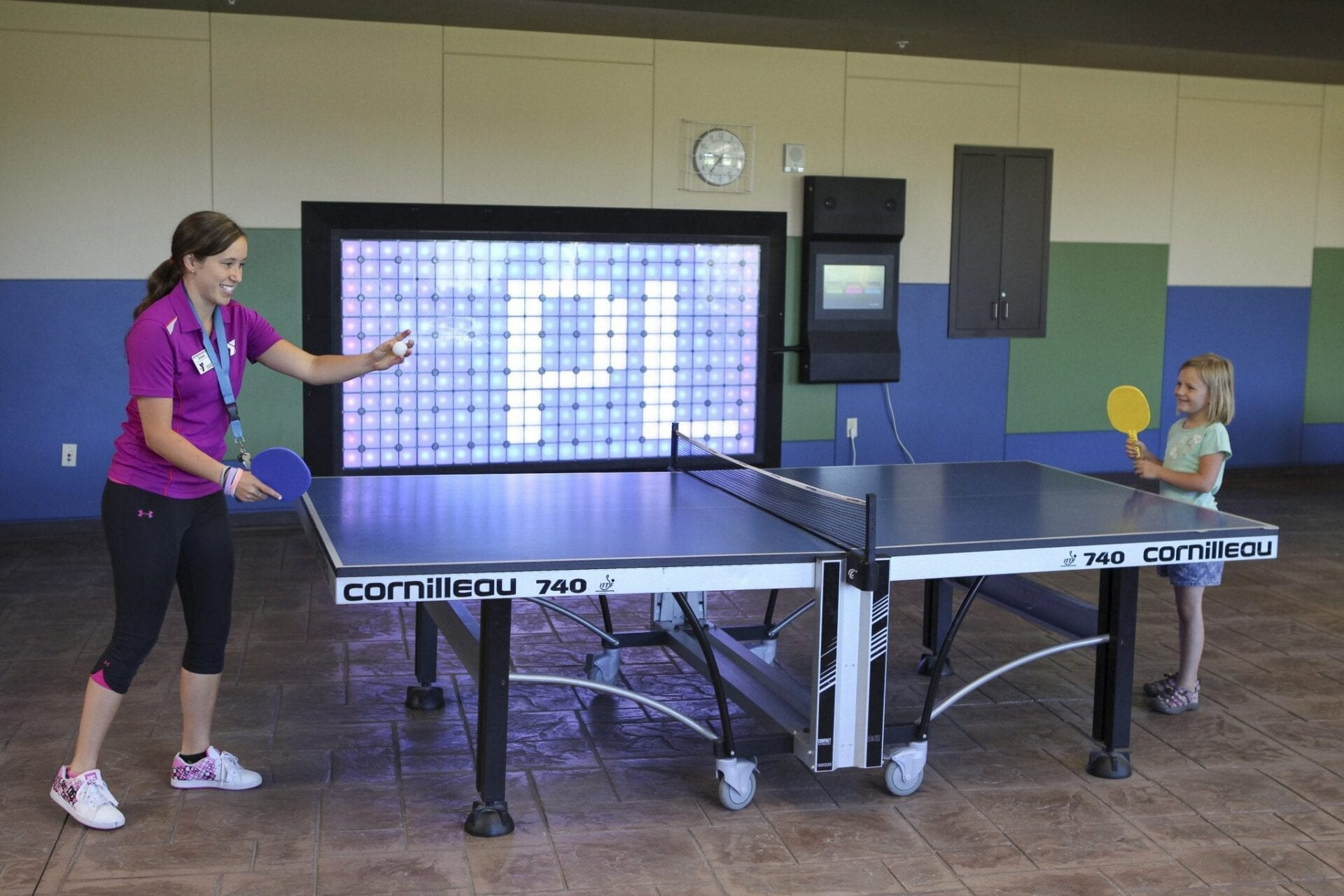North FAC staff playing ping pong with child