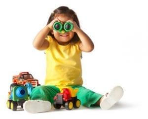 child looking through toy binoculars - Children's Center