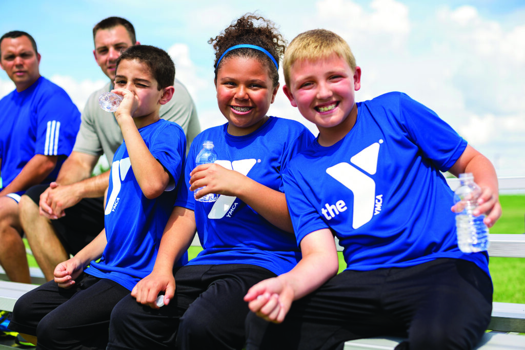 Kids on a bench taking a break from a youth activity wearing blue YMCA shirts